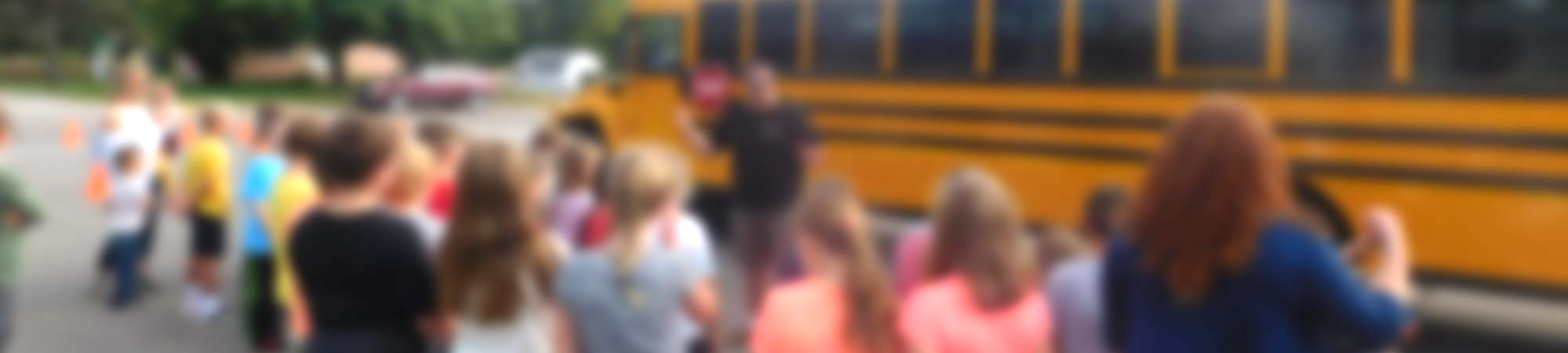 Blurred photo of an Aksamit bus driver performing a school bus safety class with a group of children